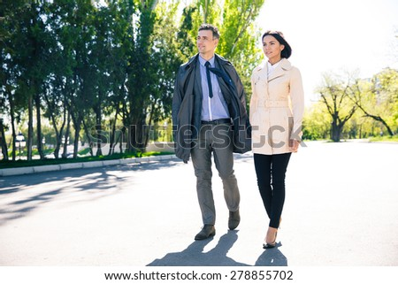 Portrait of a beautiful couple walking in park - stock photo