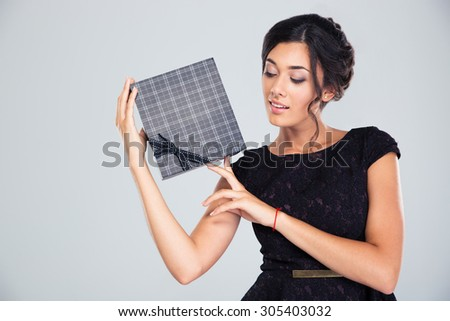 Portrait of a beautiful cute woman holding gift box on gray background