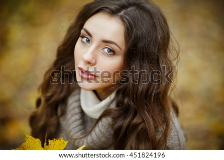 Portrait of a beautiful, dreamy and sad girl with long wavy hair in a knit sweater, close-up, autumn - stock photo
