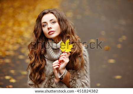 Portrait of a beautiful, dreamy and sad girl with long wavy hair in knit sweater autumn - stock photo