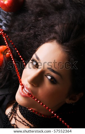 Portrait of a beautiful eccentric woman biting a red beads - stock photo