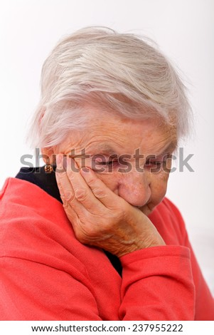 Portrait of a beautiful elderly lady sitting on her bed - stock photo
