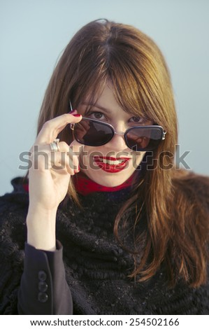 Portrait of a beautiful elegant young woman with red lipstick looking over her sunglasses. - stock photo
