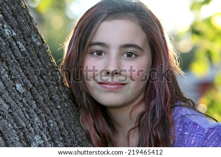 Portrait of a beautiful eleven year old girl smiling outside. - stock photo