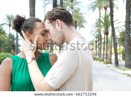 Portrait of a beautiful ethnically diverse young tourist couple hugging holding heads together visiting a destination city avenue with palm trees on summer holiday. Travel recreation lifestyle.