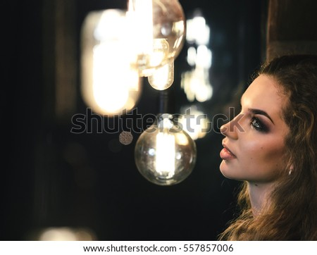 Portrait of a beautiful European girl. A woman stands near a wall surrounded by Edison's light bulbs.