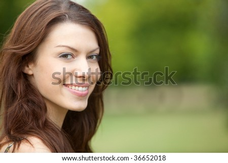 Portrait of a beautiful european woman smiling outdoors - stock photo