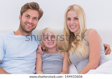 Portrait of a beautiful family in bed - stock photo