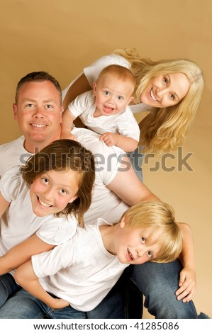 Portrait of a beautiful family of five all snuggled together in white tee shirts and jeans