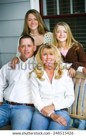Portrait of a beautiful family sitting on their front porch swing.