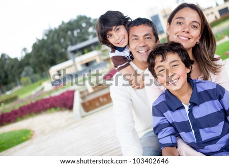 Portrait of a beautiful family smiling outdoors - stock photo