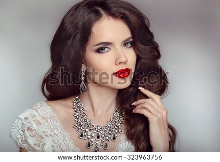 Portrait of a beautiful fashion bride girl with sensual red lips. Wedding make up and waving hair. Studio background. Luxury modern style.  - stock photo