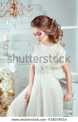 Portrait of a beautiful fashion bride in studio.Perfect wedding make up and hairstyle.Wedding accessories on shiny blonde hair.Romantic girl in white elegant long dress dreaming and looking down.  - stock photo
