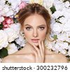 Portrait of a beautiful fashion bride, sweet and sensual. Wedding make up and hair. Flowers background. Art modern style. Blue eyes. Natural manicure. - stock photo