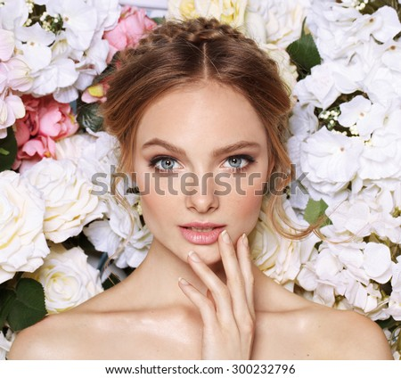Portrait of a beautiful fashion bride, sweet and sensual. Wedding make up and hair. Flowers background. Art modern style. Blue eyes. Natural manicure.