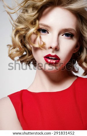Portrait of a beautiful fashion model face with red lips in red dress - stock photo