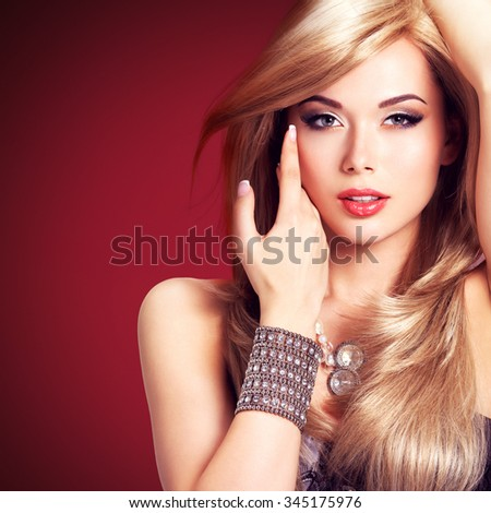 Portrait of a beautiful  fashion woman.  Pretty sexy face of a glamour girl posing at studio with silver accessor. - stock photo