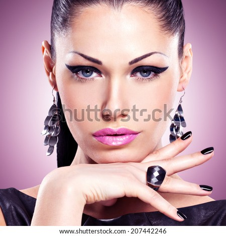 Portrait of a beautiful  fashion woman with black nails and bright makeup.  Pretty sexy face of a glamour girl posing at studio over art color background - stock photo