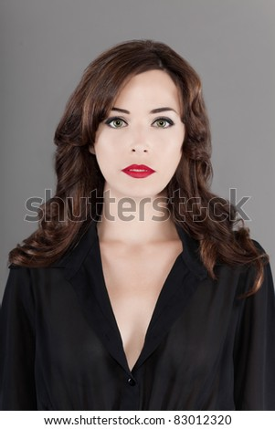 Portrait of a beautiful fashionable woman serious  in studio isolated on gray background - stock photo