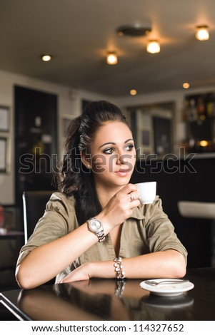 Portrait of a beautiful fashionable young brunette woman having coffee. - stock photo