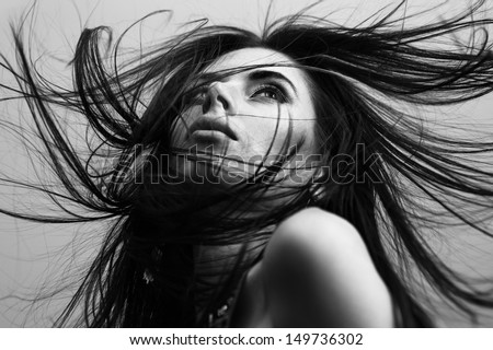 Portrait of a beautiful fashionable young girl with flying hair
