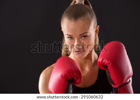 Portrait of a beautiful female boxer. Pretty woman in red boxing gloves looking so serious.