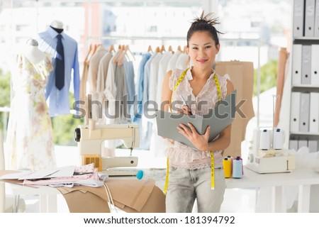 Portrait of a beautiful female fashion designer with folder in the studio - stock photo