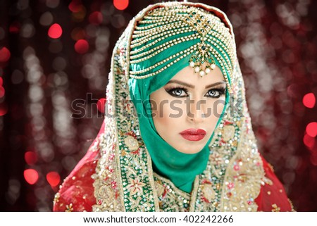 Portrait of a beautiful female model in traditional ethnic asian indian bridal costume with heavy makeup and jewellery - stock photo