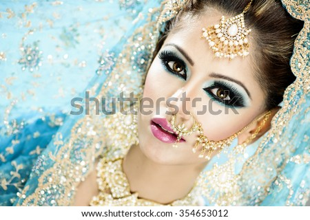 Portrait of a beautiful female model in traditional indian bride outfit with makeup and jewellery - stock photo