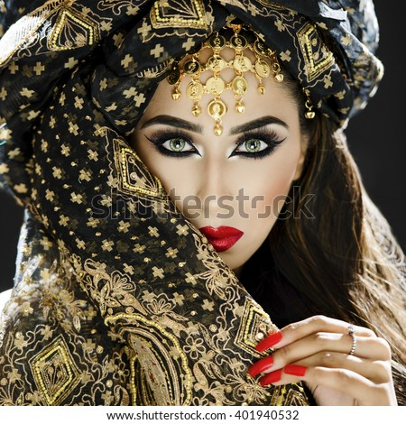 Portrait of a beautiful female model wearing a turban and veil in heavy eye makeup and jewellery - stock photo