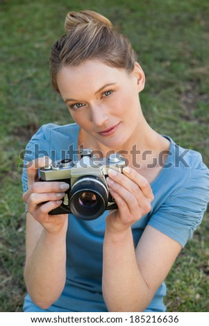 Portrait of a beautiful female photographer standing at the park