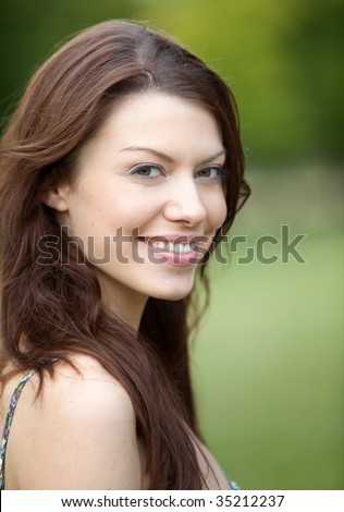 Portrait of a beautiful female smiling outdoors - stock photo