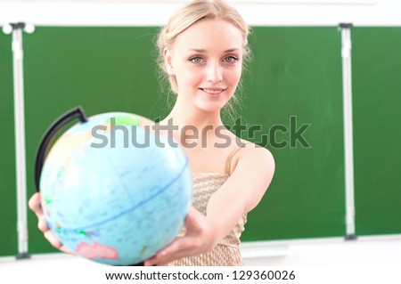 portrait of a beautiful female teacher with a globe - stock photo
