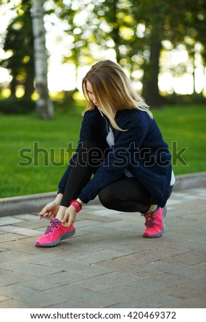 Portrait of a beautiful fit woman tying the laces on her running shoes in green park on sunny summer day, athletic female tie shoelaces while taking break between evening jog in the fresh air - stock photo