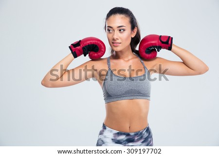 Portrait of a beautiful fitness woman standing in boxing gloves isolated on a white background