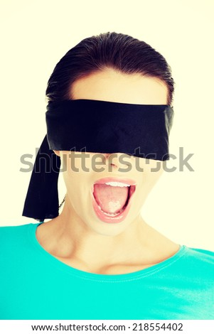 Portrait of a beautiful frighten young blindfold woman screaming - stock photo