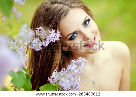 Portrait of a beautiful gentle girls with wavy hair and bright make-up around sprigs of lilac, close-up - stock photo