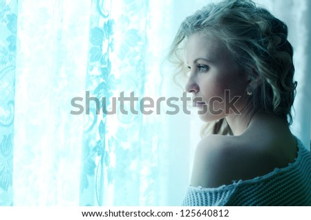 portrait of a beautiful girl at the window in the early morning - stock photo