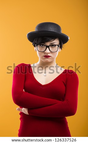 Portrait of a beautiful girl bored with something, wearing a hat and nerd glasses - stock photo