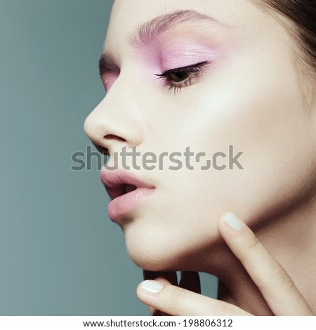 Portrait of a beautiful girl face in profile against a blue background - stock photo
