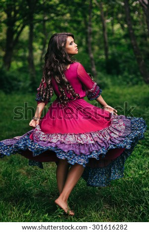 Portrait of a beautiful girl gypsy in violet dress - stock photo