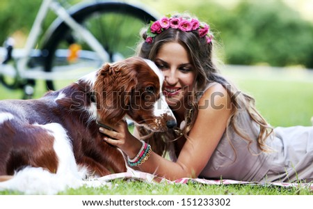 Portrait of a beautiful girl hanging out with a dog in a park - stock photo