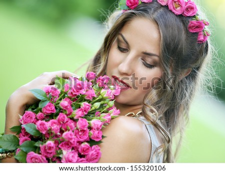 Portrait of a beautiful girl holding bouquet of flowers in the park
