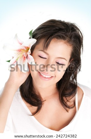 Portrait of a beautiful girl holding tropical flower in hand close to her face - stock photo