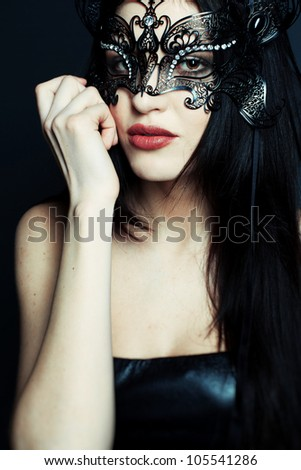 Portrait of a beautiful girl in a black dress with a theatrical mask on her face - stock photo