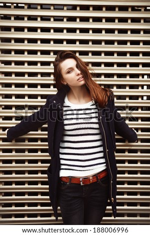 ... of a beautiful girl in a coat on a wall background - stock photo