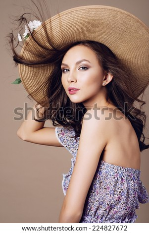 Portrait of a beautiful girl in a hat and dress, posing in studio on a beige background, the concept of health and beauty