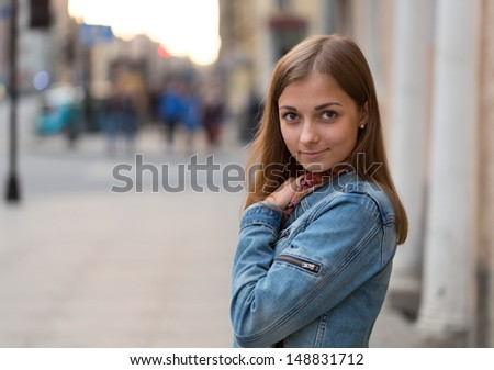 portrait of a beautiful girl in a jeans jacket on the street at night - stock photo