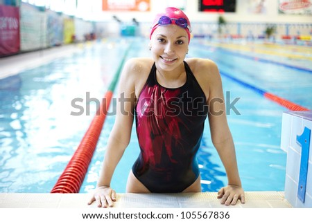 Portrait of a beautiful girl in a red cap at the swimming pool - stock photo