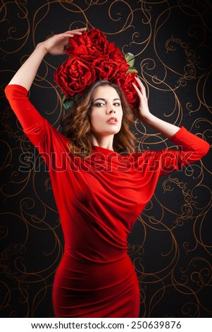 Portrait of a beautiful girl in a red dress with a wreath of flowers